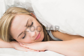 Closeup of beautiful woman under sheet with eyes closed in bed
