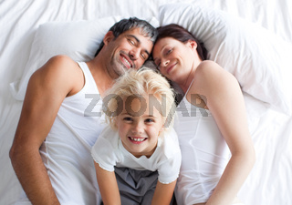 Little girl on bed with her parents smiling at the camera