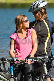 Happy teen bikers embracing at lakeside