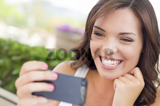Young Adult Female Texting on Cell Phone Outdoors