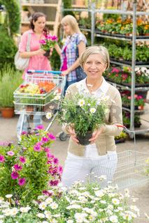 Garden centre senior lady hold potted flower