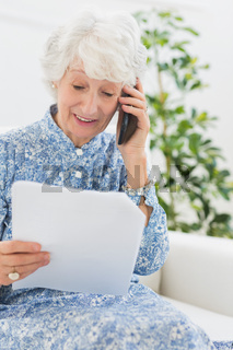 Elderly happy woman reading a paper on the phone
