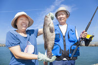 happy senior couple fishing and showing big grouper