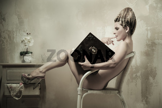 Naked woman sitting in a chair reading a book indoors