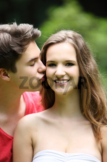 Teenage boy kissing his pretty girlfriend