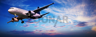 Jet aircraft in a sunset sky. Panoramic composition.