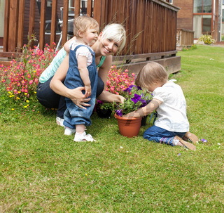 Smiling woman with two children in the garden