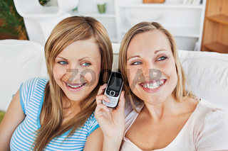 Two bright women using a cellphone at home