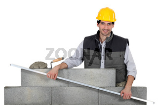 Bricklayer with a steel rule