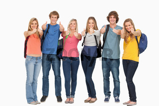 Smiling group giving a thumbs up as they wear backpacks
