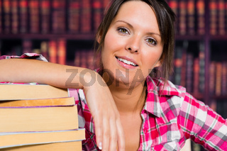 Girl leaning on books with a smile