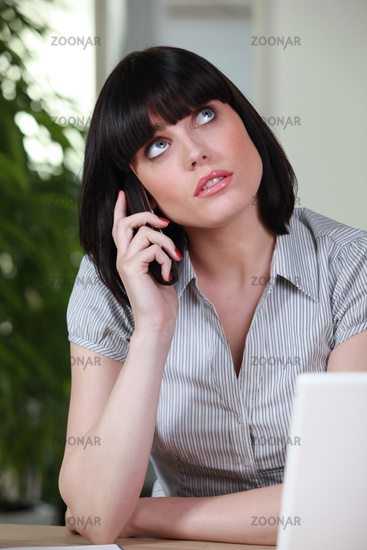 Beautiful young woman pensive on phone