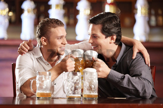 Two drunken gay men with a beer in a pub