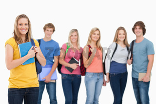 A group of college students standing as one girl stands in front of them