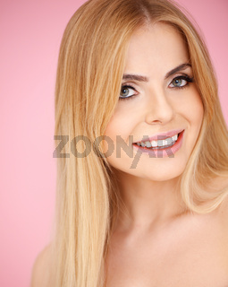 Smiling blond girl on pink