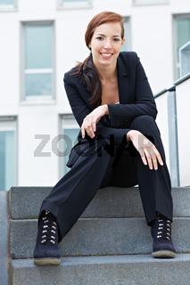 Studentin sitzt auf einer Treppe