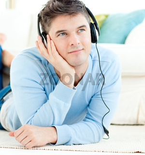 Positive man with headphones lying on the floor