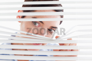 Cute businesswoman peeking through a venetian blind