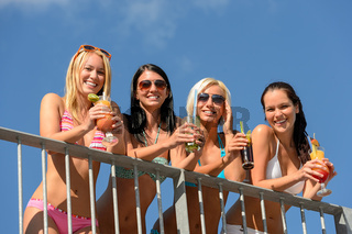 Beautiful women in bikinis smiling with drinks
