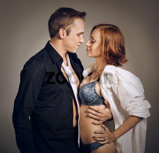 Beautiful young smiling couple in love embracing indoor, studio shot