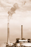 Smokestacks of power station on sky background. Sepia
