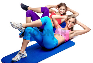 Two beautiful girls doing abdominal exercise
