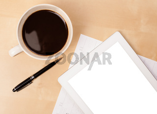 Tablet pc with empty space and a cup of coffee on a desk