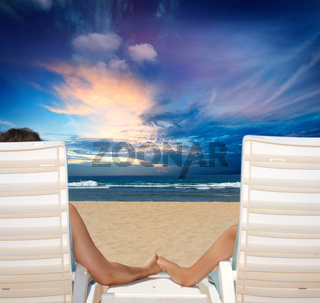 Couple in beach chairs holdi hands on beach  and enjoy sunset