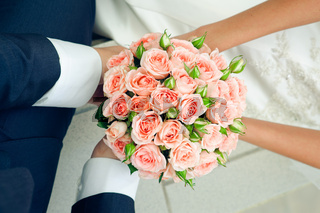 hand in hands with rose bouquet. Wedding couple