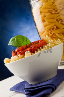 Pasta with tomato sauce on blue background