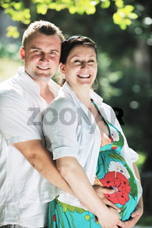 Happy pregnant couple at beautiful sunny day in park