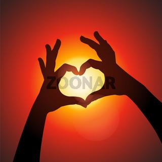 Love shape hands silhouette in sky