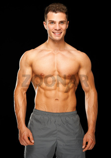 Portrait of muscular sporty man standing on black
