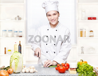 Young chef cutting onions in kitchen