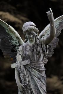 Weiblicher Friedhofsengel mit Kreuz und Palmzweig sowie erhobenem Arm und gestrecktem Zeigefinger | Cemetery female angel with cross and palm branch, raised arm and outstretched index finger