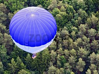 Heissluftballon schwebt über Waldfläche