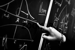Pointing on chalk board in black and white