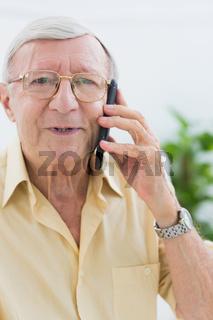 Smiling elderly man calling someone
