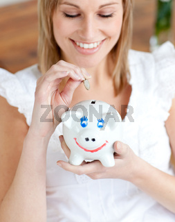 Cheerful woman saving money in a piggy-bank
