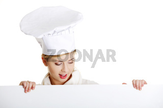 Happy woman cook or baker looking over paper sign billboard.