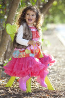 happy smiling little girl in colourful clothes sitting outdoors in chair