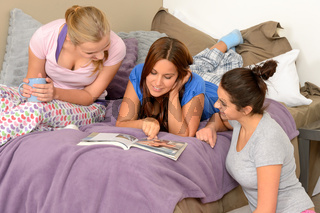 Three teenage girls reading at slumber party