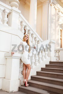 Beautiful blond woman in white dress on the stairs