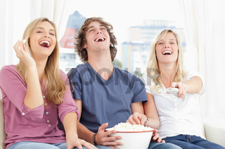 Three friends eating popcorn while laughing at the show