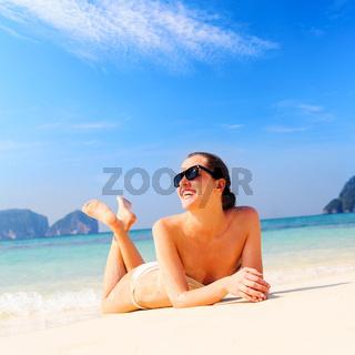 woman is lying on beach