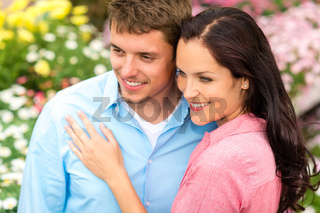 Happy couple embracing in nature garden