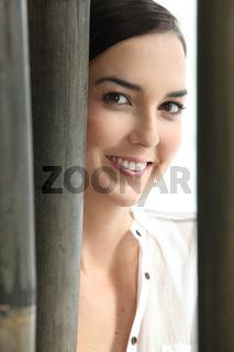 Young woman smiling hidden behind bamboos