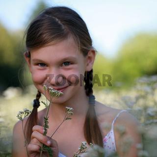 Mädchen riecht an einer Blume