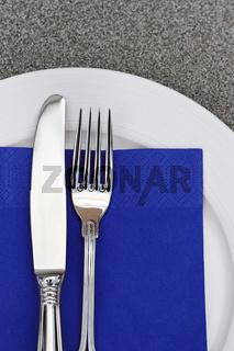 Teller mit Besteck und blauer Serviette