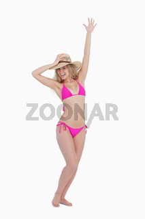 Smiling young woman holding her hat with one arm raised